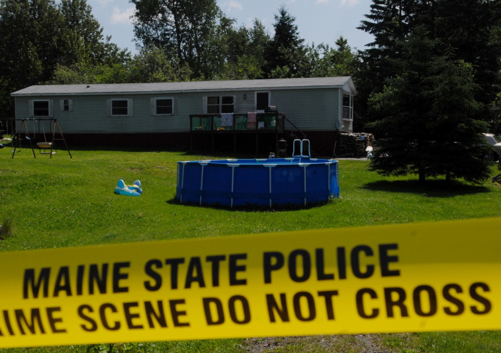 Exterior photo of crime scene: On Friday morning, members of the Maine State Police Evidence response team continued to look for clues at the Amity home where two men and a young boy were stabbed to death Wednesday night. Crime tape continued to surround the site Friday. (Bangor Daily News/John Clarke Russ)