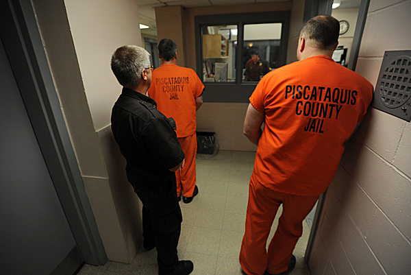 Piscataquis County corrections officer Jeffery Starbird, left, waits in a hallway with two inmates  before escorting them back to their cells during mail and medication call at the booking room of the jail on Wednesday, 23, 2010. Piscataquis County's jail budget has been slashed by $50,000 by the Department of Corrections.  (Bangor Daily News/Kevin Bennett)