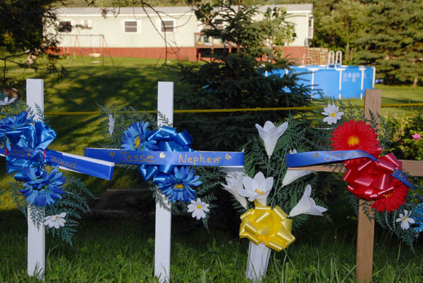 By late Friday afternoon,  three memorial crosses, as well as flower arrangements, were placed along Route 1 in Amity -- in front of the mobile home where 10-year-old Jesse Ryan, his father Jeffrey Ryan, 55,  and Jason Dehahn, 30, were found dead Wednesday night.  The Maine State Evidence Response Team was at the scene all day Friday as they continued to look for leads. BANGOR DAILY NEWS PHOTO BY JOHN CLARKE RUSS
