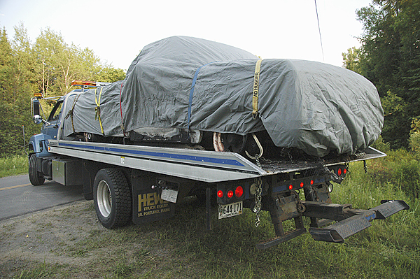 The pickup truck missing since three people were found dead, victims of an apparent triple homicide, in an Amity trailer on Wednesday is carried on a flatbed truck away from a clearing in Weston on Saturday. BANGOR DAILY NEWS PHOTO BY NICK SAMBIDES JR.