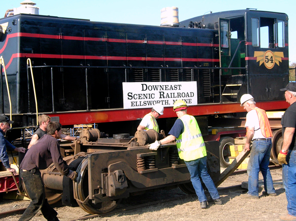 Volunteers from the Downeast Scenic Railroad join a crew from Baxter Cook House and Building Movers of Searsport Wednesday to roll the wheel assembly into place as they prepare to unload a 70-ton locomotive that was delivered to the railroad at its Washington Junction location. The locomotive will power the railroad's planned scenic trips between Ellsworth and Ellsworth Falls beginning next summer. (Bangor Daily News/Rich Hewitt)