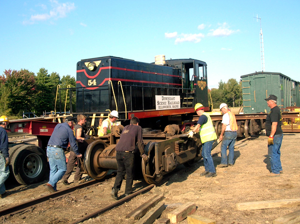 Volunteers from the Downeast Scenic Railroad join a crew from Baxter Cook House and Building Movers of Searsport on Wednesday to roll the wheel assembly into place as they prepare to unload a 70-ton locomotive that was delivered to the railroad at its Washington Junction location. The locomotive will power the railroad's planned scenic trips between Ellsworth and Ellsworth Falls beginning next summer. (Bangor Daily News/Rich Hewitt)