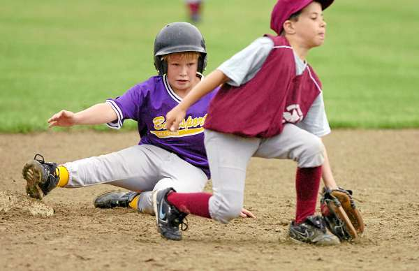 Bucksport's Tanner Stegner (left) slides safely into second ahead of a tag from Ellsworth's Zach Harris during Tuesday's Little League baseball game in Bucksport. (Bangor Daily News/Bridget Brown)