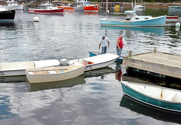 Mike Bernier (left) and Joe Sargent tie up a dinghy after mooring the Master Simon in Winter Harbor on Thursday, July 1, 2010, a day after the lobster boat, captained by Phil Torrey, collided with another lobster boat near Pond Island which left fellow Winter Harbor fisherman Frank Jordan, 71, dead and Jordan's boat, the Linda Diane, sunk. (Bangor Daily News/Bridget Brown)