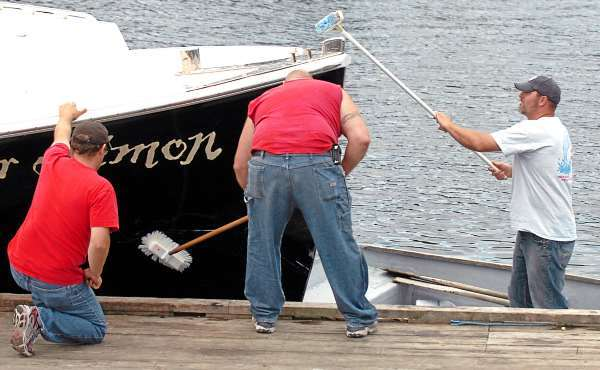 Josh Joyce (from left), Joe Sargent and Mike Bernier help clean the Master Simon in Winter Harbor on Thursday, July 1, 2010, a day after the lobster boat, captained by Phil Torrey, collided with another lobster boat near Pond Island which left fellow Winter Harbor fisherman Frank Jordan, 71, dead and Jordan's boat, the Linda Diane, sunk. (Bangor Daily News/Bridget Brown)