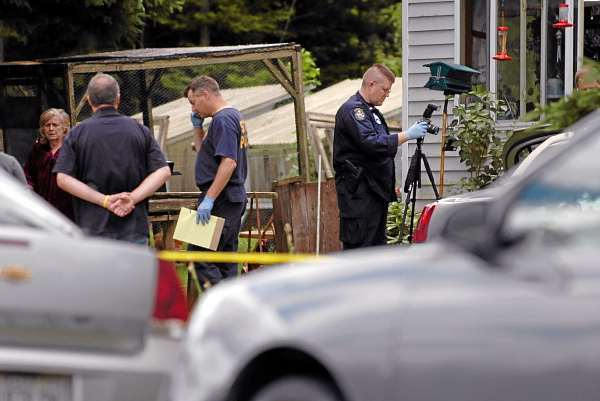 Maine State Police Evidence Response Team members collect evidence from a residence on U.S. Route 1 in Orient on Friday, July 2, 2010 in connection with last week's triple homicide. (Bangor Daily News/Bridget Brown)