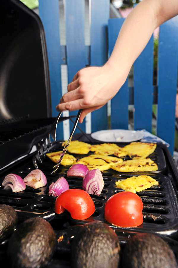 Advacados, tomatoes, onions, and pineapple are tended on a grill in a Bangor backyard on Wednesday, June 30, 2010. (Bangor Daily News/Kevin Bennett)