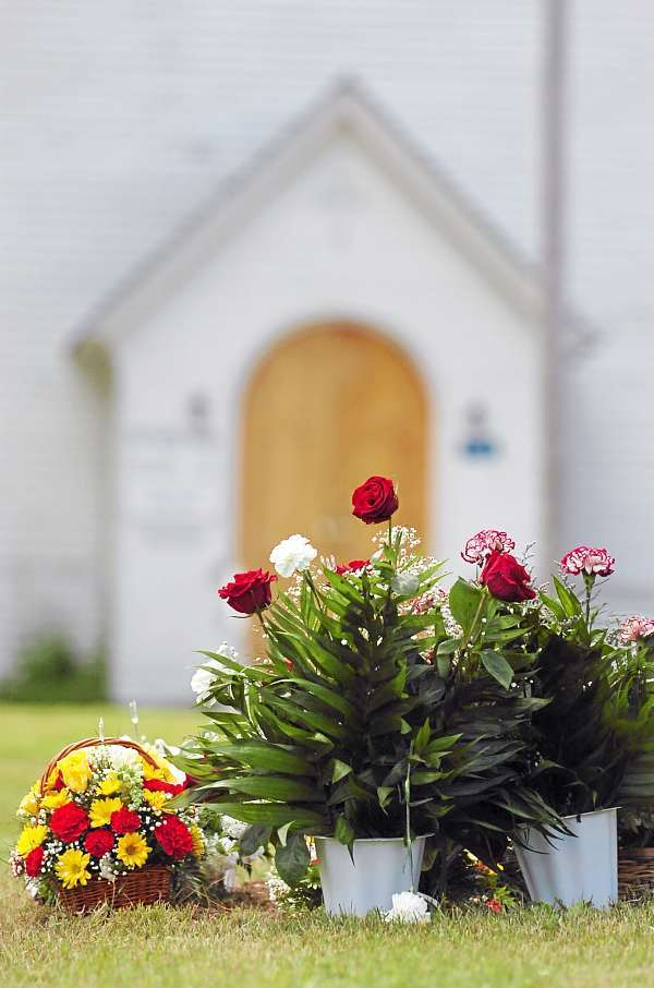 Several memorial flowers are seen on Jesse Ryan's grave in Amity on Friday, July 2, 2010. (Bangor Daily News/Bridget Brown)