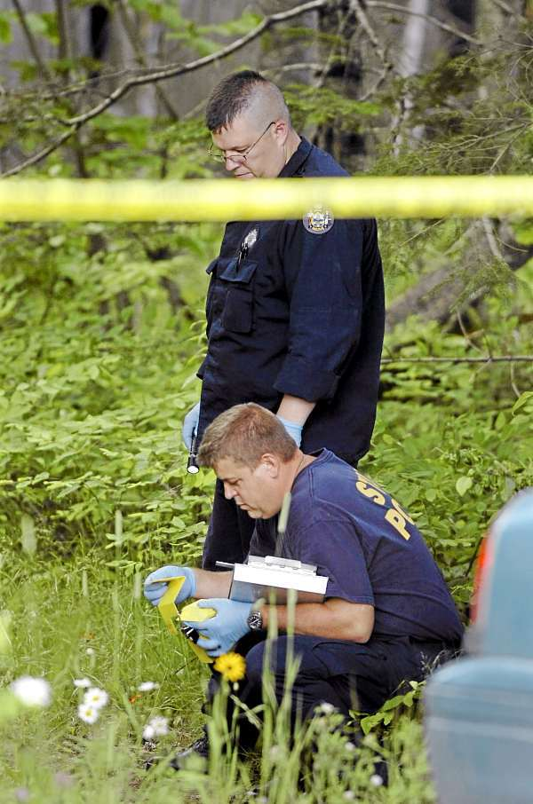 Maine State Police Evidence Response Team members collect evidence from a property on the Amity-Orient town line on U.S. Route 1 Friday, July 2, 2010 in connection with last week's triple homicide. (Bangor Daily News/Bridget Brown)