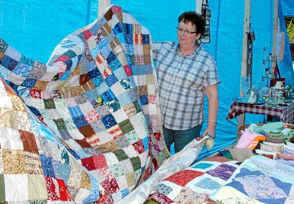 Daphne O'Leary of Mars Hill checks out a home-made quilt at Rhonda Caron's yard sale in St. John Plt. &quotThere's as much socializing as there is selling or buying this weekend,&quot Caron said. JULIA BAYLY PHOTO