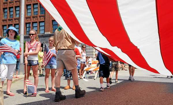 People watch as the Boyscout Troup 42 from Hampden marhes by with a huge flag during the Fourth of July parade in Bangor Sunday.   (Bangor Daily News/Gabor Degre)