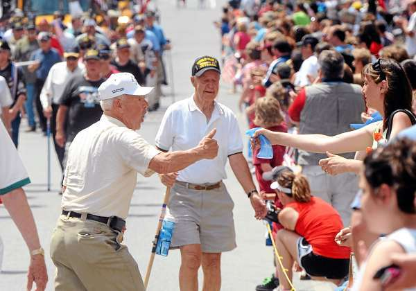 World War II veteran William Harrigan, 83 (left) gives a thumb up to a woman who sprayed him with a little water to cool down while marching in the Fourth of July parade in Bangor Sunday.  Harrigan who lives in Bangor and Portland served in the Navy and fought in the second World War for three and a half years. (Bangor Daily News/Gabor Degre)