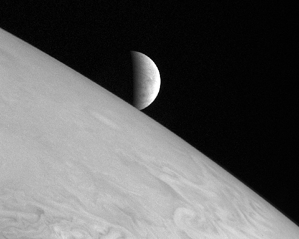 Europa rises over the horizon of Jupiter in this photo taken by the New Horizons spacecraft in 2007. Visable is the cracked surface of Europa's expansive ice fields, just behind a jumble of Jupiter's swirling clouds.  PHOTO COURTESY OF NASA, Johns Hopkins U. APL, SWRI