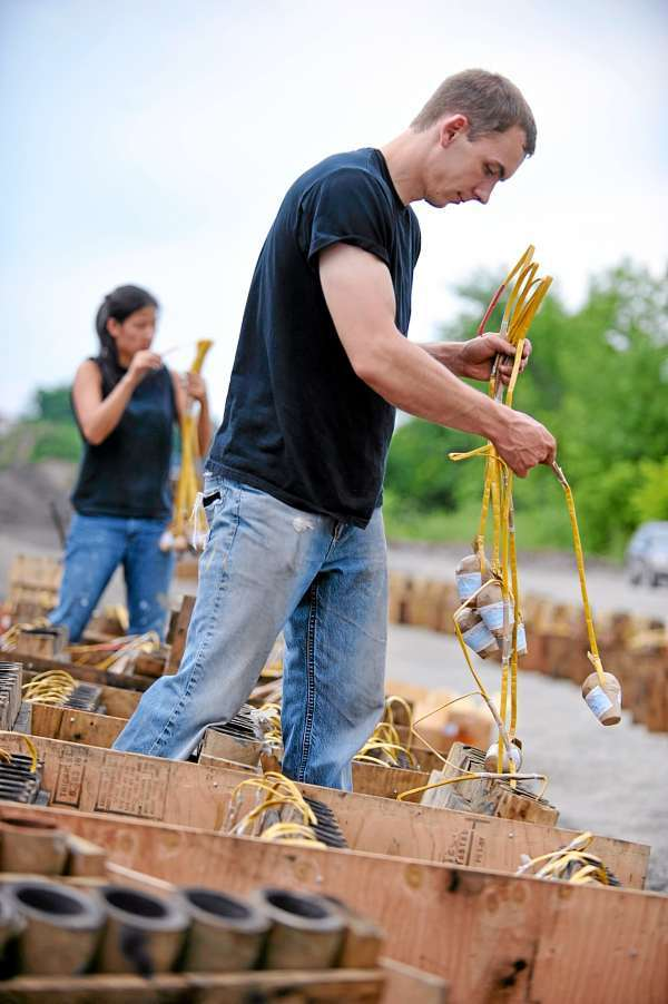 Matt Pietraszewski (in foreground) of Sidney and Kristen Gabor of Bangor load firework shells into their tubes during Central Maine Pyrotechnic's set-up for Bangor's Fourth of July firework show at dusk  Sunday. The Central Maine Pyrotechnic crew brought 1400 rounds of shells for Sunday evening's pyrotechnic display on Bangor's waterfront which they planned to last more than 20 minutes. (Bangor Daily News/John Clarke Russ)