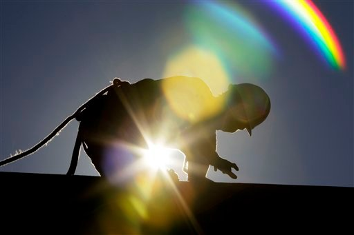 A construction worker is backlit from the morning sun while working on a roof in the heat in Chapel Hill, N.C., Tuesday, July 6, 2010. After an extended Fourth of July weekend when temperatures inched into at least the 90s from Maine to Texas and into the Southwest and Death Valley, the mid-Atlantic is embarking on a string of intensely hot days, with temperatures in some places closing in on 100-plus degrees. Temperatures could reach as high as 102 degrees on Tuesday, meteorologists said, and Wednesday was forecast to be the most humid day of the stretch. (AP Photo/Gerry Broome)