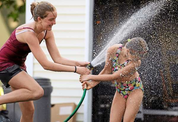 Sisters, Emma, left, and Grace Henry, right, of Bangor fight over the family garden hose as they cool down at their family's Forest Avenue home during Tuesday's high temperature. The reported high temperature at the Bangor International Airport was 90 degrees on Tuesday. (Bangor Daily News/Kevin Bennett)