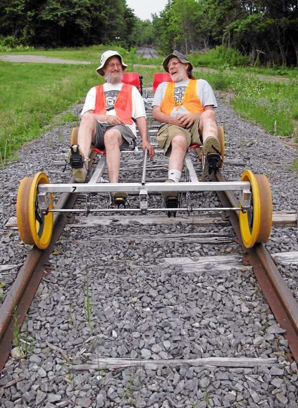 Volunteer rail-cycle conductors Kip Penney (left) and Doug Nye demonstrate the custom-built contraptions on a recent Sunday evening in Thorndike, Maine. Rail-bike excursions on the former Belfast & Moosehead Lake Railroad tracks will be offered this summer through the Brooks Preservation Society. (Abigail Curtis/Bangor Daily News)