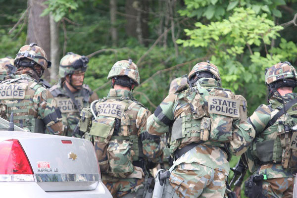 A state police tactical squad in the woods near the Department of Veterans Affairs Medical Center at Togus on Thursday, July 8, 2010, where a Medway veteran was killed by police.