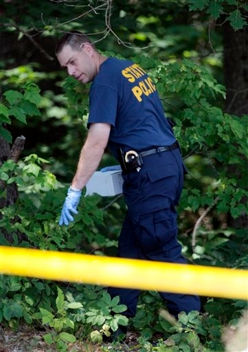 Maine State Police officers collect evidence at the scene.
