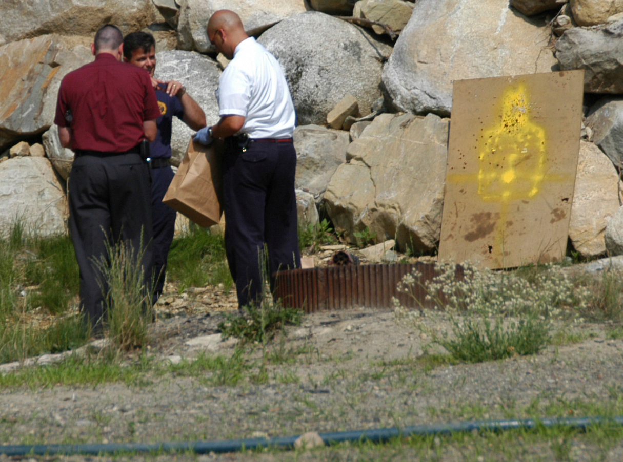 State police Detective Sgt. Troy Gardner [maroon shirt], state police Trooper Thomas Fiske [left] and state police Detective Darryl Peary gather evidence at a makeshift target range outside 49 Grindstone Road in Grindstone on Thursday in connection with the shooting death of James F. Popkowski, 37, of Medway, at the Togus VA clinic.