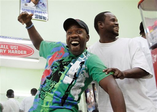Miami Heat basketball fan Harry James Labissiere, center, and a customer in his Miami barbershop celebrate Thursday, July 8, 2010, as NBA free agent LeBron James announces his decision on television to join the Miami Heat. (AP Photo/J Pat Carter)