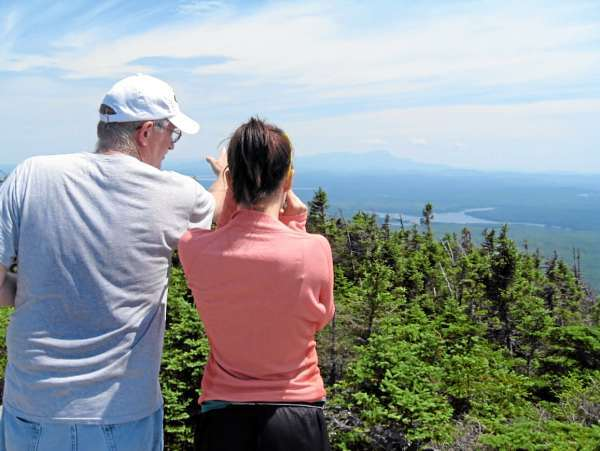 Steve Hasty points out the view of Ragged Lake and Katahdin in the distance to his daughter, (name not given), from the summit of Big Spencer Mountain east of Moosehead Lake.