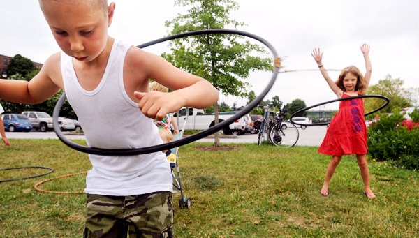 Ian Reid, 8, (left) and his sister Ainsley, 5, of Brewer try their hoola hoop skills while at the Bangor Waterfront during the third annual Penobscot River Revival Saturday.  Heather Reid, Ian and Ainsley's mother said that this is the first time they came to the event, but she will try to visit in the coming years, beacuse it is  very kid friendly. (Bangor Daily News/Gabor Degre)