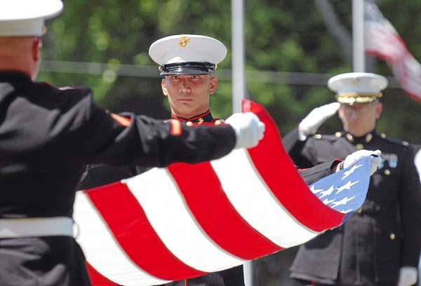 Cpl. Matthew D'Alessando (left) and Staff Sgt. Joseph Justice (center) fold a flag which was given to the family of Lt. James Popkowski, 37, a former Marine, at his interment Tuesday, July 13, 2010 at Grindstone Road Cemetery in Medway. Popkowski died last week in a shooting involving law enforcement officials in Augusta that is currently under investigation. (Bangor Daily News/Bridget Brown)