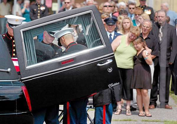 As family and friends look on, a military honor guard escorts the casket of former Marine Lt. James Popkowski, 37, following his funeral service at St. Peter's Catholic Church in East Millinocket on Tuesday, July 13, 2010. Popkowski died last week in a shooting involving law enforcement officials in Augusta that is currently under investigation. (Bangor Daily News/Bridget Brown)
