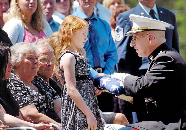 Maj. Michael Henderson presents Vianca Popkowski, 8, the daughter of Lt. James Popkowski, 37, with a flag at the former Marine's interment Tuesday, July 13, 2010 at Grindstone Road Cemetery in Medway. Popkowski died last week in a shooting involving law enforcement officials in Augusta that is currently under investigation. (Bangor Daily News/Bridget Brown)