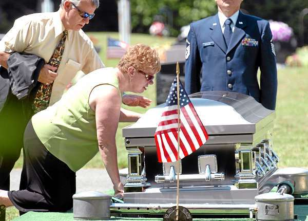 Deabra Deschaine gives a kiss to her son and former Marine Lt. James Popkowski, 37, at his interment Tuesday, July 13, 2010 at Grindstone Road Cemetery in Medway. Popkowski died last week in a shooting involving law enforcement officials in Augusta that is currently under investigation. (Bangor Daily News/Bridget Brown)