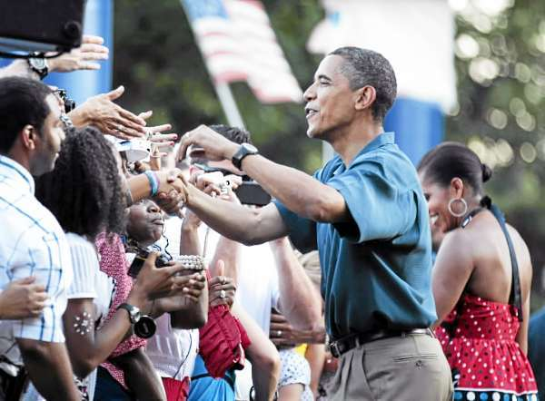 President Barack Obama, center, and first lady Michelle Obama, right, greet members of the United States Armed Forces and their families as they host an Independence Day celebration on the White House's South Lawn, Sunday, July 4, 2010 in Washington.   (AP Photo/Manuel Balce Ceneta)