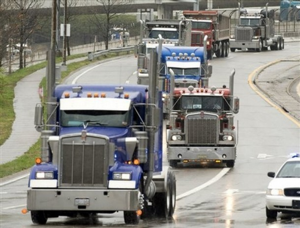 **FILE** In this April 4, 2008 file photo, trucks file down Greenbrier Street as truckers rally against high fuel prices at the West Virginia state Capitol in Charleston, W.Va. Struggling with record diesel prices, the trucking industry's main trade group on Thursday, May 8, 2008, introduced a plan to reduce fuel consumption and emissions over the next decade mainly by having its members slow down. (AP Photo/Bob Bird, File)