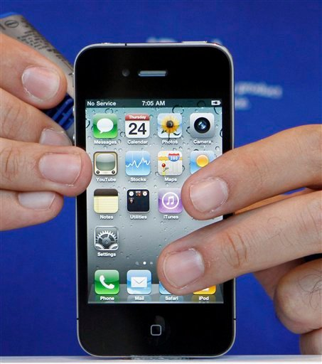 FILE - In this file photograph taken June 24, 2010, an Apple store employee displays a new Apple iPhone 4 in Miami Beach, Fla. Consumer Reports said Monday, July 12, 2010, the iPhone 4 has reception problems caused by its antenna design.(AP Photo/Alan Diaz, file)