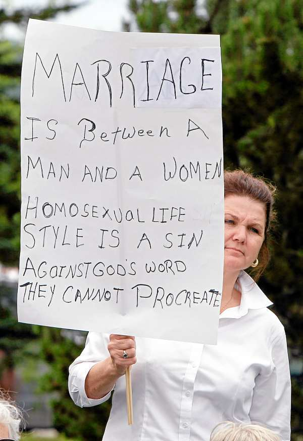An attendee at a rally for opponents of same-sex marriage holds a sign in Capitol Park, Wednesday, July 14, 2010, in Augusta, Maine. The National Organization for Marriage kicked off its &quotOne Man, One Woman&quot bus tour in Maine, where residents last year rejected a law that would have allowed same-sex couple to wed. (AP Photo/Robert F. Bukaty)