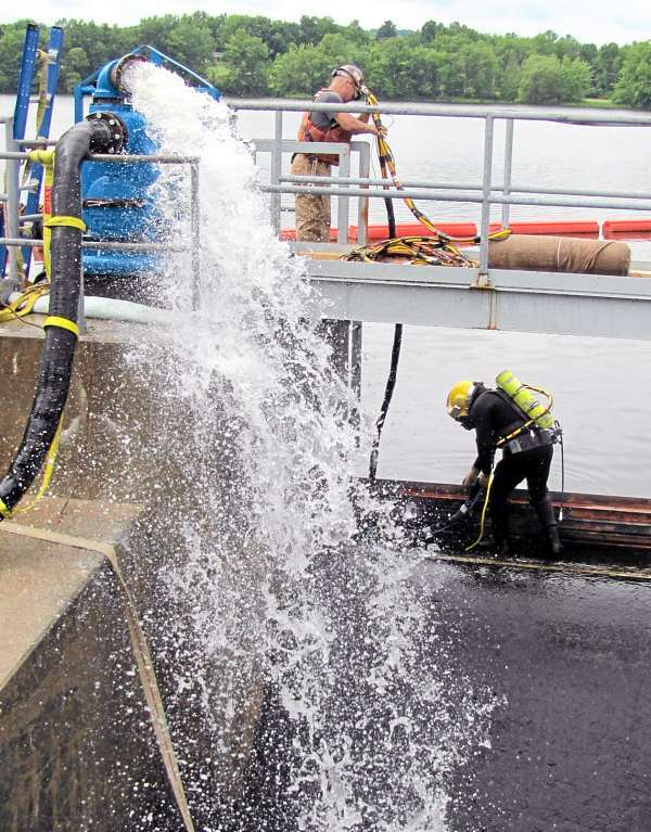 Jeff Campbell, a diver from Pepperrell Cove Marine of Portsmouth, N.H., prepares to jump into the water near the Sebasticook Lake dam Wednesday afternoon, July 14, 2010. Matt Smith, shown above Campbell, tends an air hose and communication line to ensure the diver's safety. Campbell's mission was to plug holes in a temporary barrier that has been installed in an effort to draw down the water level around the dam's gate, which was damaged last month when a support chain snapped. (Bangor Daily News/Christopher Cousins)