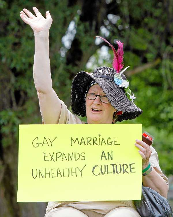Madelyn  Fijalek, of Farmington, Maine, holds a sign at a rally for opponents of same-sex marriage in Capitol Park, Wednesday, July 14, 2010, in Augusta, Maine. The National Organization for Marriage kicked off its &quotOne Man, One Woman&quot bus tour in Maine, where residents last year rejected a law that would have allowed same-sex couple to wed. (AP Photo/Robert F. Bukaty)