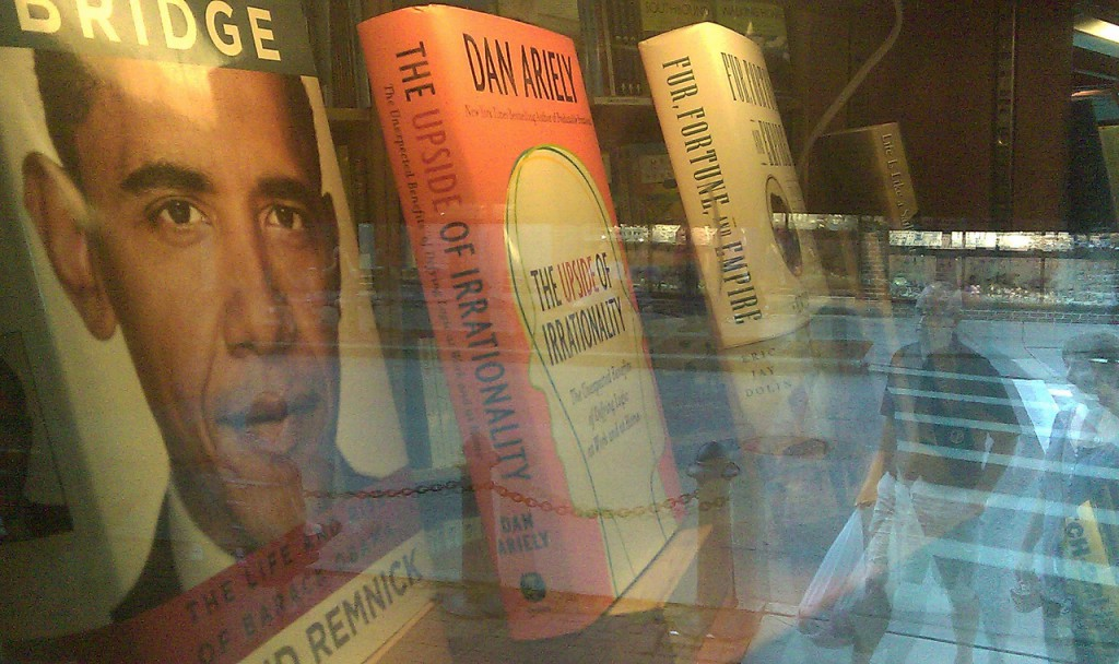 The image of President Obama and the reflection of passing pedestrians are visible Wednesday evening in a window of a bookstore in downtown Bar Harbor. Obama and his family are expected to arrive Friday on Mount Desert Island for two days of vacation.  Bill Trotter photo