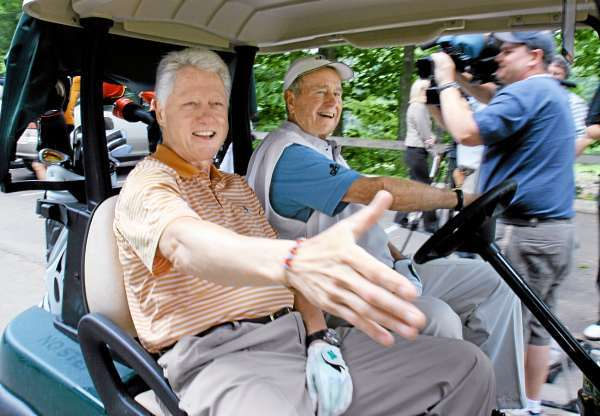 ** FILE ** Former President Bill Clinton, left, reaches to shake a hand of a well wisher as he and former President George H.W. Bush head off to start a round of golf at the Cape Arundel Golf Club in Kennebunkport, Maine in this  June 28, 2005 file photo. One Clinton jets to Alaska and Iraq with Republicans, and enthusiastically sponsors legislation with GOP lawmakers who impeached her husband. The other plays golf with former President Bush and accepts assignments from the current one. All this bipartisan snuggling by Sen. Hillary Rodham Clinton and former President Clinton has some Democrats and Republicans questioning their motives. Is this pure, calculated politics designed to get the former first lady ready for a presidential bid in 2008? (AP Photo/Pat Wellenbach, Files)
