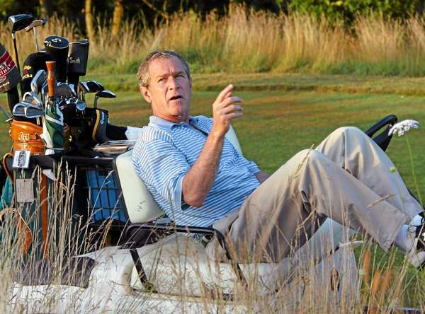 ** FILE ** In this Aug. 4, 2002 file photo, President George W. Bush stretches out in his golf cart at the Cape Arundel Golf Club in Kennebunkport, Maine.  (AP Photo/J. Scott Applewhite, File)