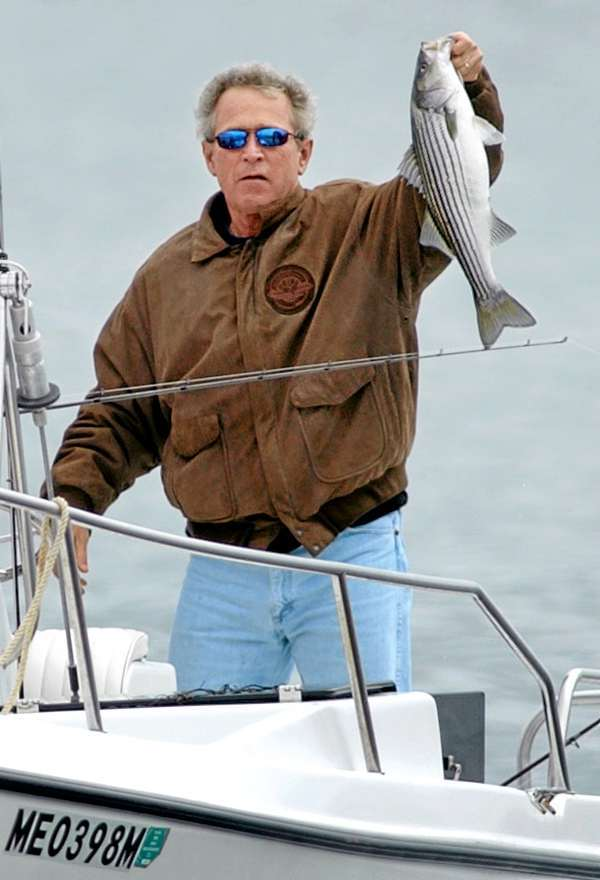 ** FILE ** In this June 14, 2003 file photo, President George W. Bush holds up a striped bass that he caught while fishing off the coast of Kennebunk, Maine.  (AP Photo/Steven Senne, File)