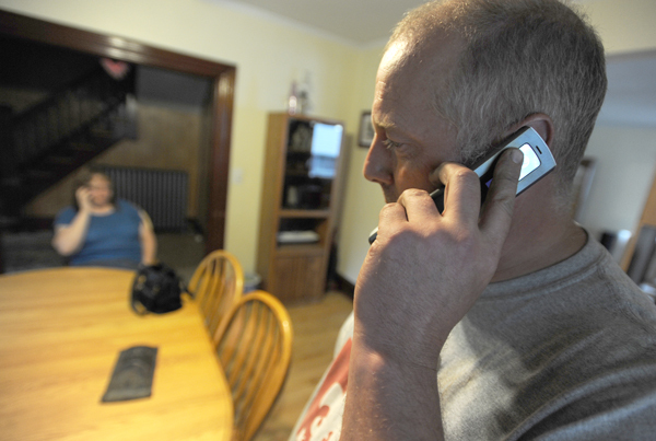 &quotMost people who want to get hold of me know to call the cell,&quot said Tyke McKay, right, as he places calls from his cell phone at his Bangor home. On the other side of the room, his wife, Kim, is also on a cell phone call.  The McKays have a total of five cell phones in their family.  They rely on cell phones and disconected their land line two years ago. (Bangor Daily News/Kevin Bennett)
