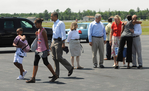 President Barack Obama walks towards the motorcade with his daughters Sasha,9, (left) and Malia, 12, (second from left) shortly after arriving at the Bar Harbor Airport Friday, July 16, 2010. On the far right First Lady Michelle Obama is greeted by Gov. John Baldacci. (Bangor Daily News/Gabor Degre)