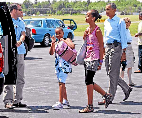President Barack Obama walks with daughters Malia and Sasha, as they arrive at Hancock County Bar Harbor Airport in Trenton, Maine, Friday, July 16, 2010. (AP Photo/Charles Dharapak)