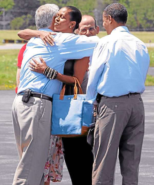 First lady Michelle Obama hugs Rep. Mike Michaud, D-Maine, as he and President Barack Obama are greeted by Maine Gov. John Baldacci at Hancock County Bar Harbor Airport in Trenton, Maine, Friday, July 16, 2010. (AP Photo/Charles Dharapak)