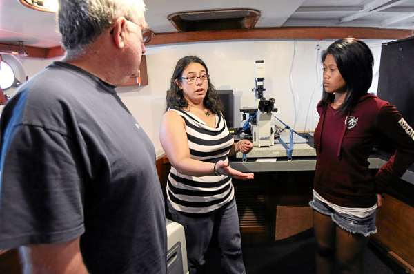University of Southern Maine student Jill Davenport, center, speaks with Steve Bugden, left, and Michaela Thurlow, as she gives a tour of the laboratory aboard the Ocean Alliance's sailboat Odyssey, Friday, July 16, 2010, in South Portland, Maine.  A group from USM teamed up with Ocean Alliance to collect tissue samples from whales in the Gulf of Mexico  to determine what toxic substances they've been exposed to. (AP Photo/Joel Page)