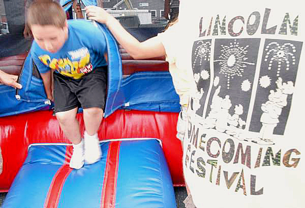A small boy leaps from the Bounce House at the 2010 Lincoln Homecoming Festival on Main Street on Friday.  BANGOR DAILY NEWS PHOTO BY NICK SAMBIDES JR.