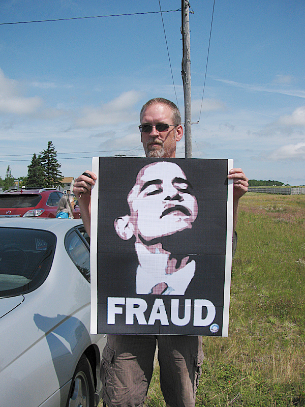 Clark Leach of Winslow, Maine, held up a protest sign Friday