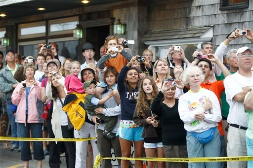 In this photo taken Friday, July 16, 2010, onlookers gather to catch a glimpse of President Barack Obama and his family as they leave a restaurant after dinner in Bar Harbor, Maine. (AP Photo/Charles Dharapak)