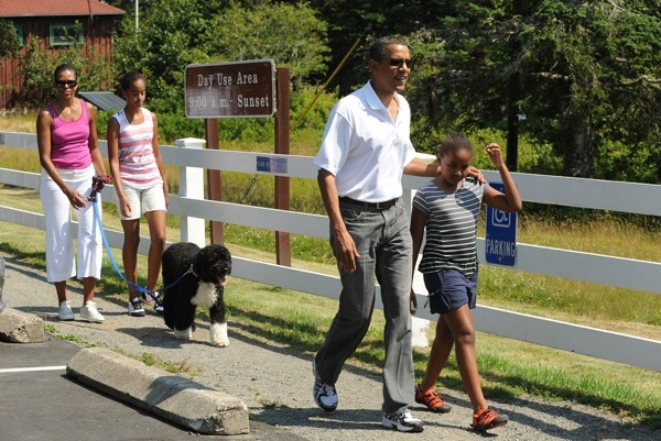 President Barack Obama Walks towards the Bass Harbor Head Light with his daughter Sasha,9, (right) as First Lady Michelle Obama walks with Malia, 12, and their dog Bo.